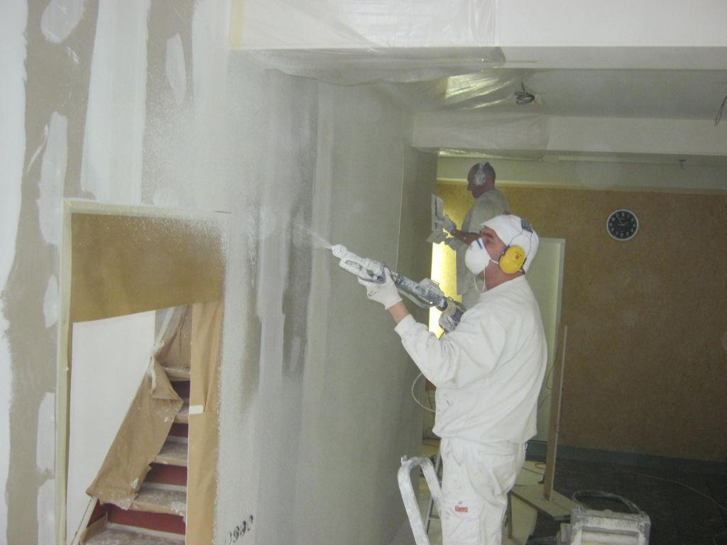 Stukadoor op de muur aan het spuiten